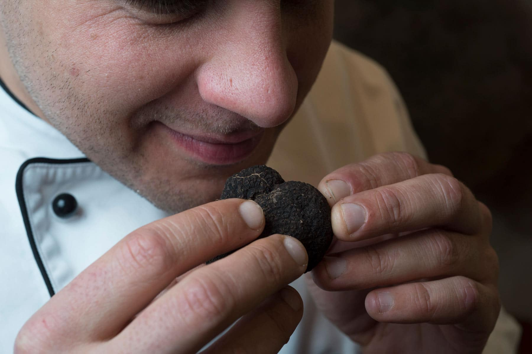 A man smells a whole black winter Canberra truffle